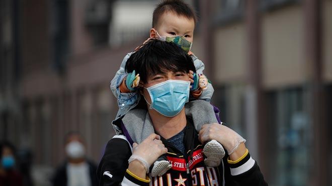 China asegura que un medicamento japonés muestra efectividad frente al coronavirus. En la foto, padre e hijo, en Beijing.