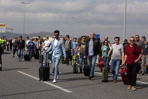 Viajeros recorriendo a pie la carretera para llegar al aeropuerto por el colapso circulatorio