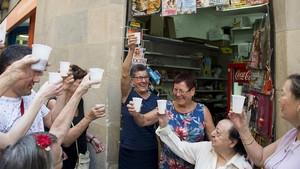 Las hermanas Consuelo (vestido azul) e Isabel Bárcena(vestido de flores)brindan con los vecinos que han ido a despedirlas.