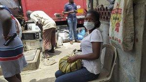 Una mujer descansa con una mascarilla este juevevs en un concurrido mercado de Lagos, Nigeria.
