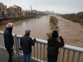 Tres vecinos observan la espectacular crecida del río Besòs, debido al temporal 'Gloria'.