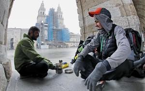 Dos peregrinos checos que llegaron desde Bordeauxse cobijan del frío con un hornillo debajo de los arcos del palacio de Raxoi, en la plaza de Obradoiro.