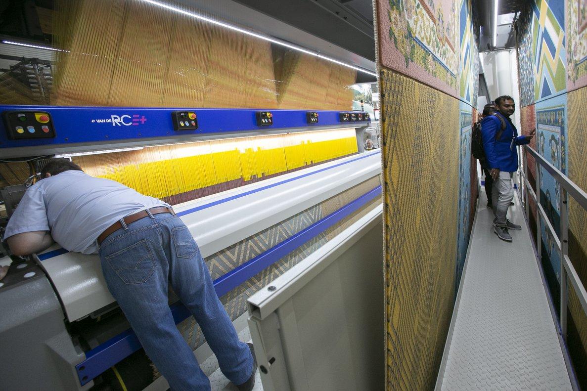 Técnicos ponen a punto una máquina de la multinacional Vandewiele en el ITMA 2019.