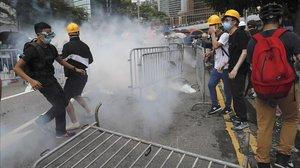 Un grupo de manifestantes reaccionan ante el lanzamiento de gas lacrimógeno durante una gran protesta contra la ley de extradición en los alrededores del Consejo Legislativo en Hong Kong.