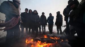 Un grupo de refugiados se protegedel frio en Bergrado, Serbia.