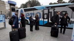 Un grupo de turistas, junto a un Aerobús en la plaza de Catalunya.