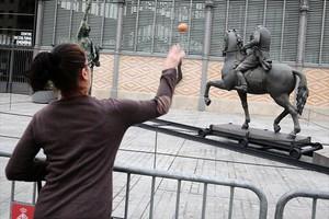 HUEVOS Una mujer prueba su puntería con la estatua de Franco.