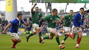 El irlandés Keith Earls corre para anotar el cuarto ensayo de su selección contra Francia.