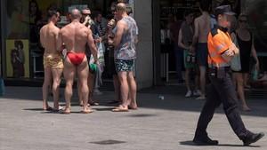 Turistas en bañador ante las tiendas, frente a un agente.