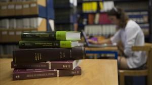 Una joven estudia en la facultad de Física y Química de la Universitat de Barcelona, junto a una pila de libros en inglés, este miércoles.