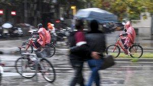 Los transeúntes se protegen de la lluvia en Barcelona.
