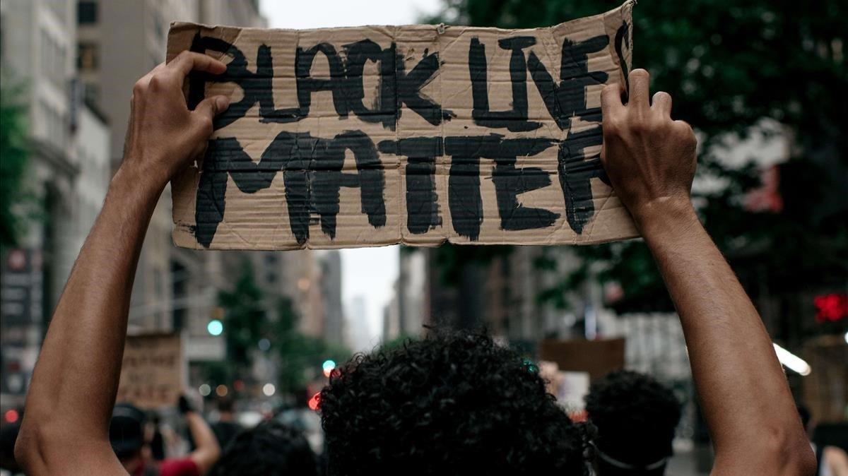 Un manifestante porta un cartel con el lema 'Black Lives Matter' (las vidas negras importan) en una manifestación en Nueva York, el 11 de junio.
