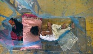 Un nino enfermo de dengue espera a recibir atencion medica cubierto con una red anti mosquitos en el gimnasio de la ciudad de Maasin, Filipinas