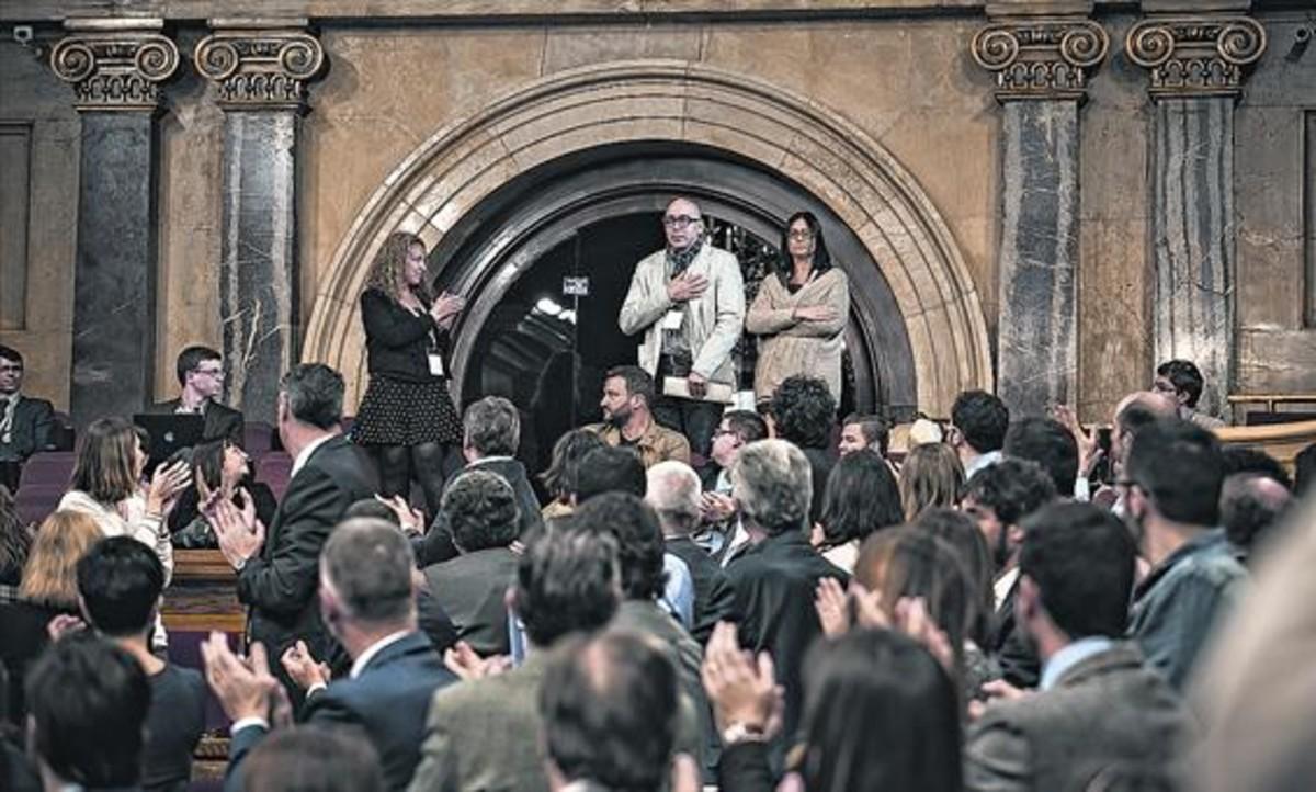 El Parlament aplaude, en marzo del 2016, a Manuel Barbero, padre del joven que sufrió abusos en el colegio marista de Sants, y su mujer, Eva Casas.