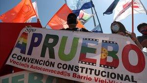 Un partidario de una nueva Constitución en Chile ondea una bandera con el lema 'apruebo', este jueves en un acto en Santiago.