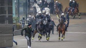 Policía montada a caballo carga contra los manifestantes ultras en Bruselas.
