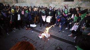 Un grupo de manifestantes prenden fuego a unas pancartas frente al Palacio Nacional de Ciudad de México en protestaporlos feminicidios.