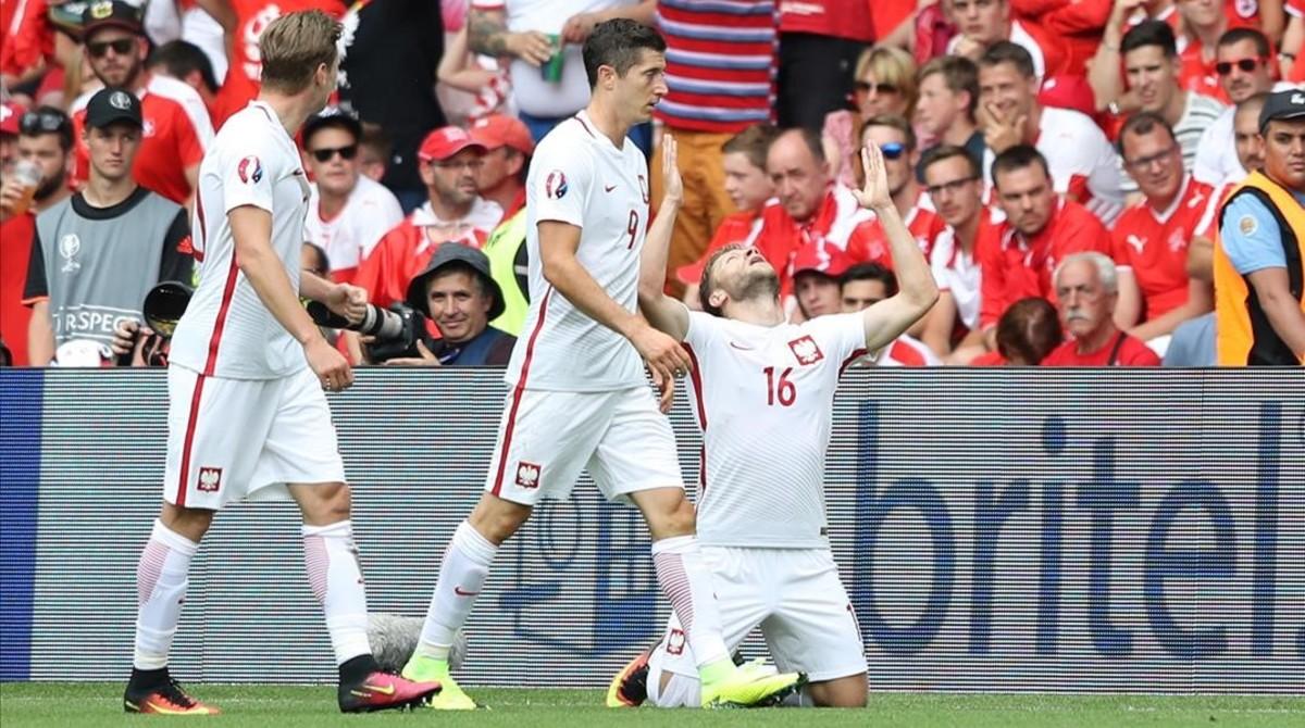 Blaszczykowski, arrodillado en el césped,celebra su gol a Suiza junto a Lewandowski.