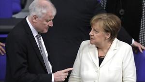 Seehofer (izq) habla con Merkel en el Parlamento alemán, en Berlín, el 14 de marzo.