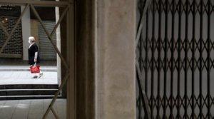 Una mujer con mascarilla pasa junto a una tienda cerrada, enLleida, el13 de julio.