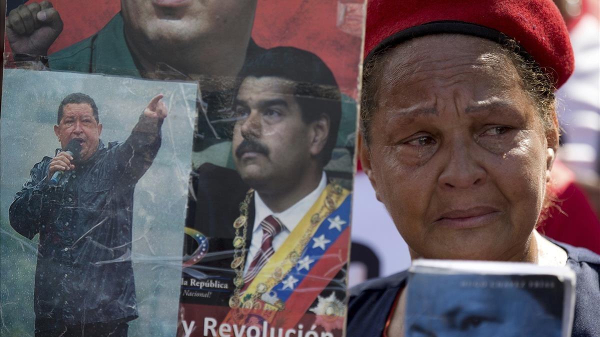 Una partidaria del chavismo llora mientras sostiene imágenes de Chávez y Maduro, durante una marcha por el quinto aniversario de la muerte de Chávez, en Caracas, el 15 de marzo.