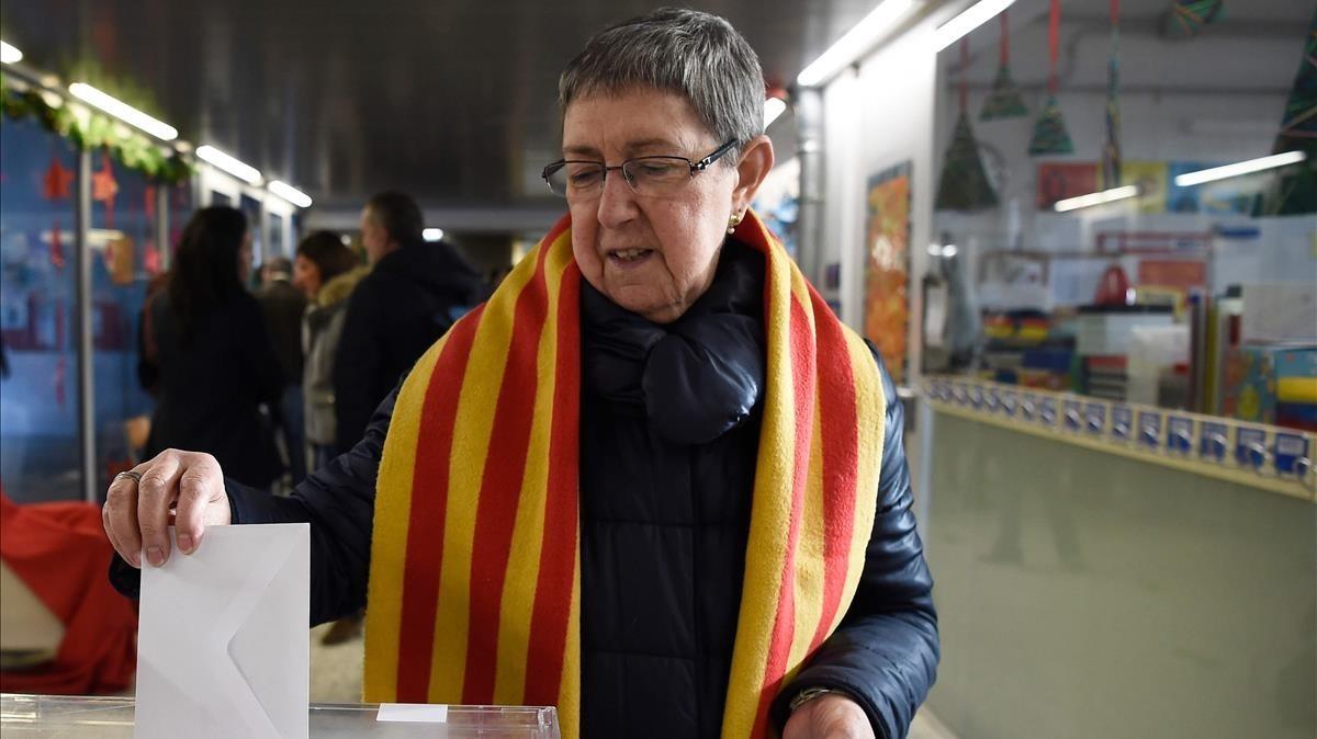 Una señora abrigada con una bufanda ejerce el voto en Sabadell.