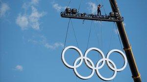Unas grúas levantan los anillos olímpicos en la zona del Obelisco este viernes.