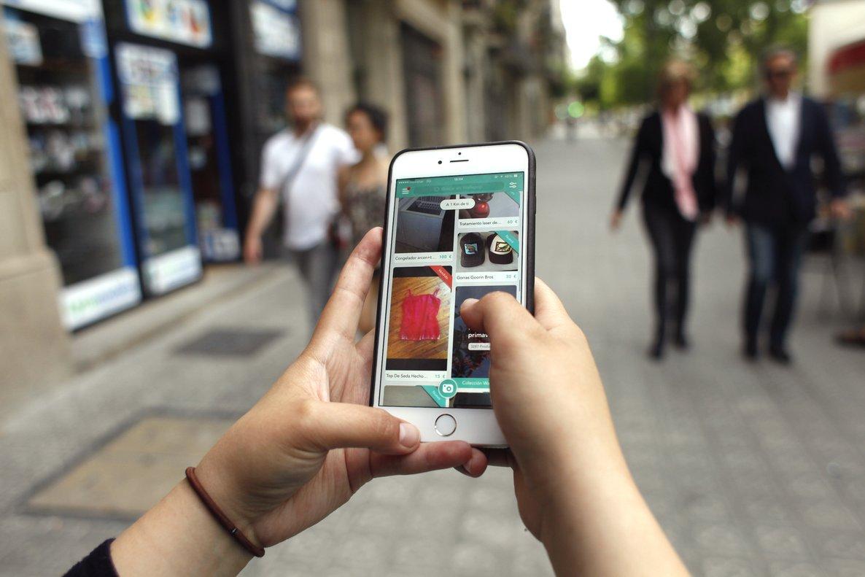 Una usuaria de Wallapop consulta la aplicación en su teléfono desde una calle de Barcelona.