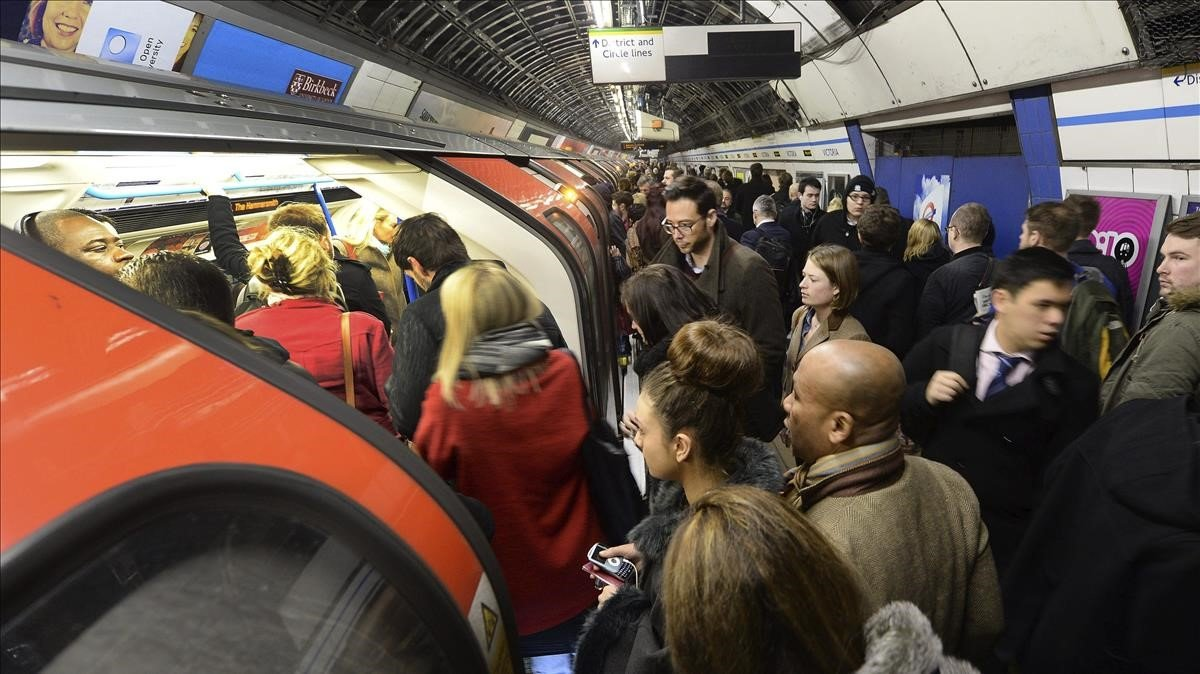 Una multitud de pasajeros espera para entrar en el metro de Londres