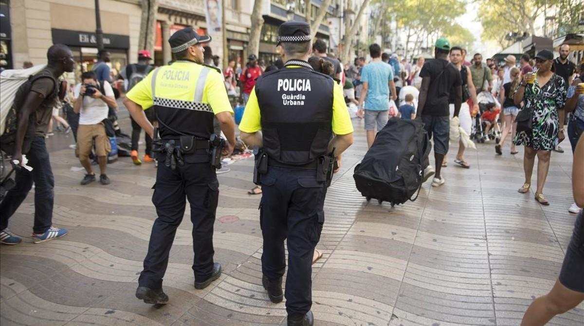 Guardias urbanos desalojan a manteros de la Rambla.