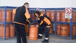 Dos trabajadores de una gasolinera del barrio de la Verneda, junto a las bombonas de butano a la venta