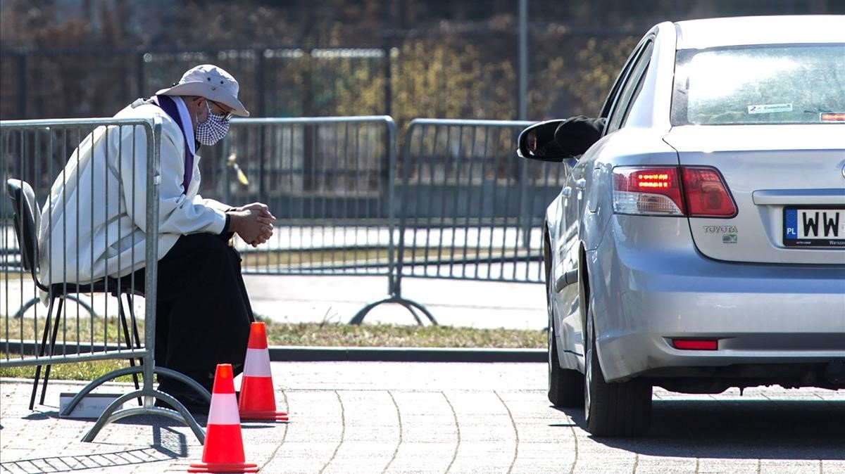 Un sacerdot polonès confessa els fidels a l'aparcament d'una església de Varsòvia