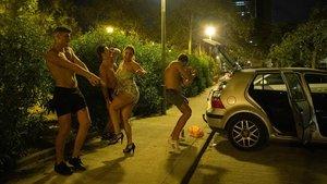 Pasadas las tres de la madrugada, cuatro jóvenes siguen con su fiesta improvisada en el párquing de la playa de la Mar Bella de Barcelona.