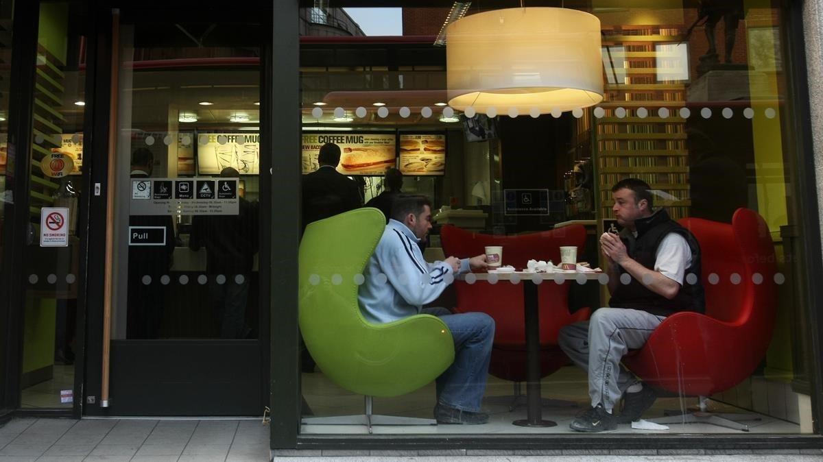 Dos personas comiendo en un establecimiento de comida rápida en Reino Unido.