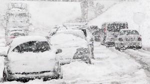 La nieve atrapa a varios vehículos en una carretera.