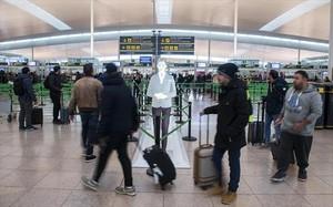Varios pasajeros se dirigen al control de seguridad antes de embarcar, ayer, en la T-1 del aeropuerto de El Prat.