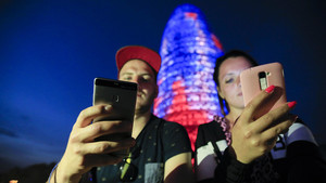 Dos personas utilizando su teléfono móvil frente a la Torre Agbar