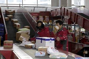 Trabajadores en una firma postal china, este miércoles 19 de febrero, en Pekín.