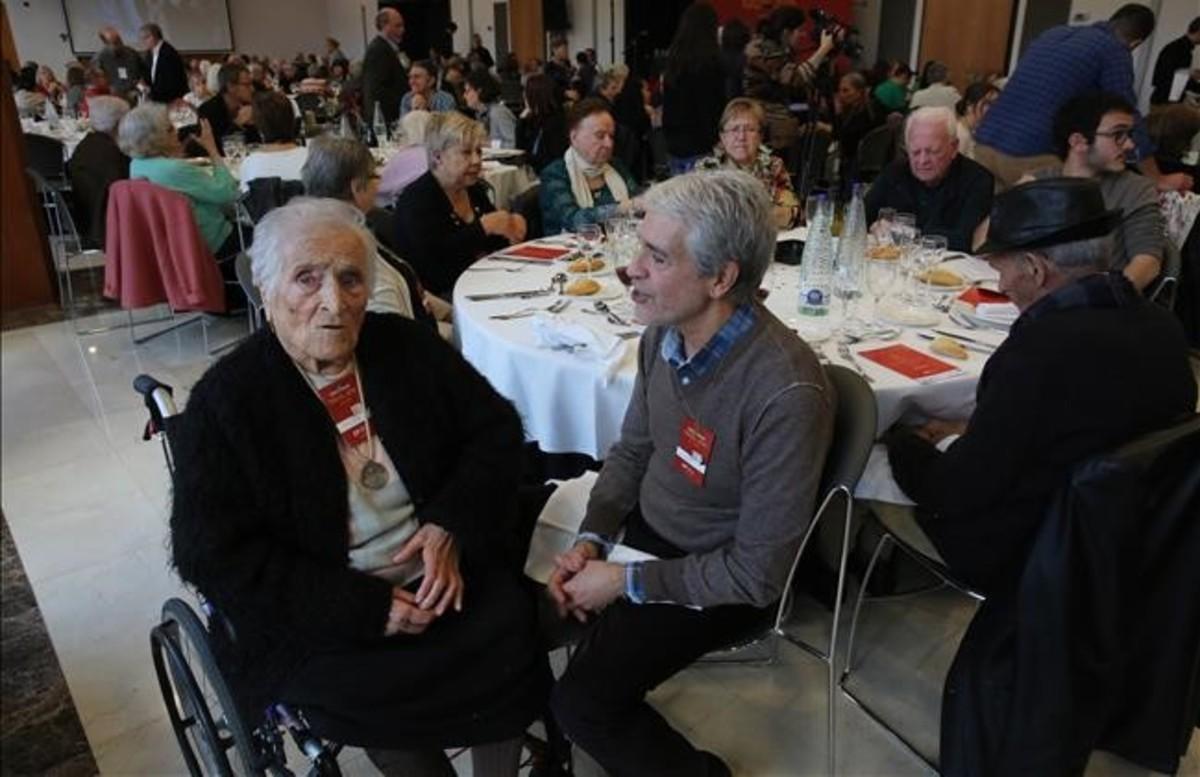 Vicenta tiene 103 años. A su lado, Robert, el voluntario de Amics de la Gent Gran que la visita cada semana desde hace cuatro años. Ambos posan el sábado durante el clásico Dinar de Nadal de la oenegé.