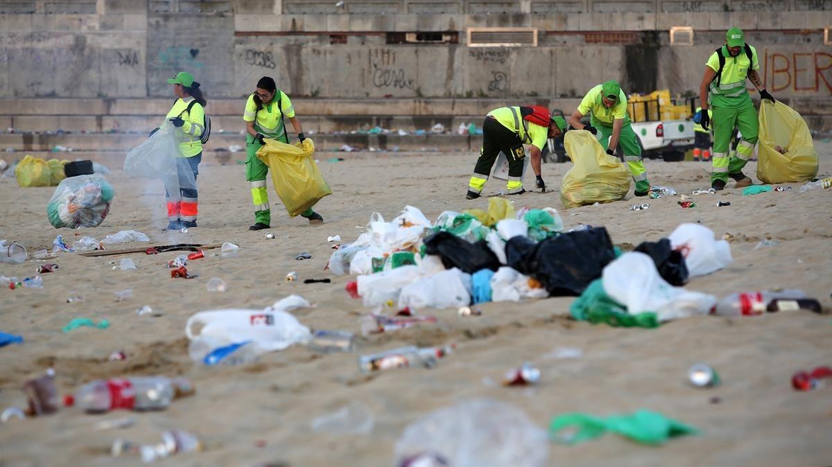 La brigada de limpieza realizando su trabajo en las playas de Barcelona, tras la verbena.