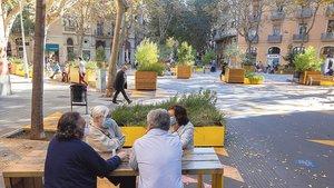 Ciudadanos conversando sentados a una de las mesas de la superilla de Sant Antoni.