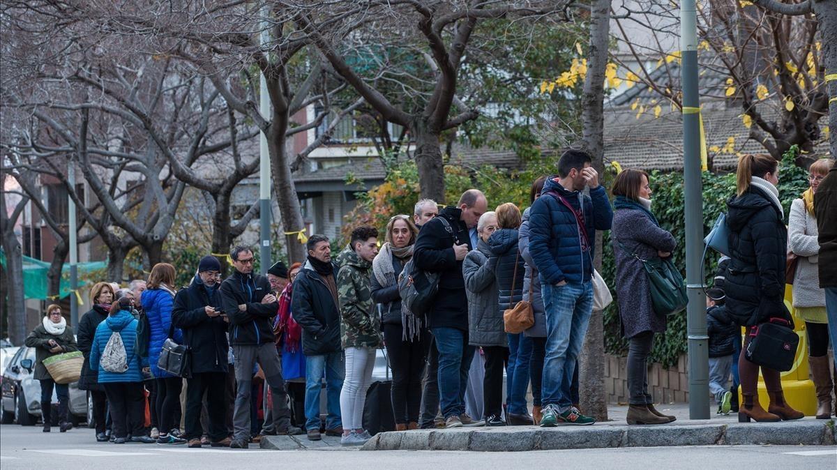 Ciudadanos esperando para votar en el colegio electoral Narcís Monturiol de Barcelona.