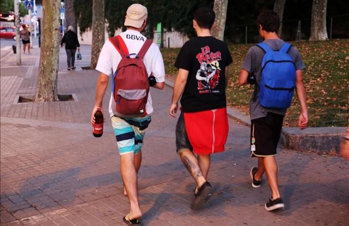 Jóvenes con botellas de cerveza buscan un rincón en el que darse al botellón antes de ir al Port Olímpic.
