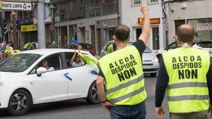 Dos trabajadores de Alcoa saludan a otros que llegan a Lugo durante la marcha de coches en caravana convocada el pasado día 28.
