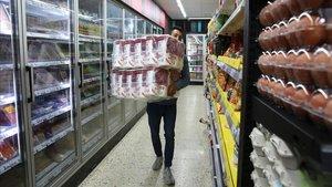 El dueño de un supermercado del barrio barcelonés de Sants repone papel higiénico, ayer.