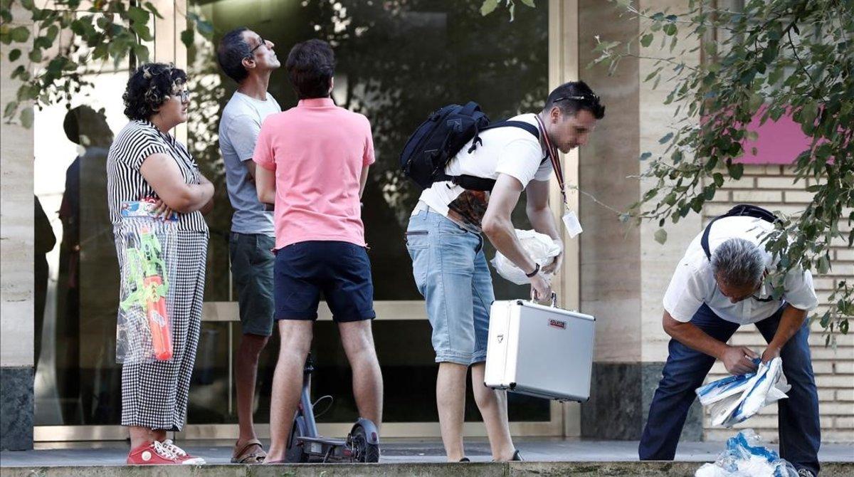 Efectivos de la policía científica trabajan en el lugar donde cayó una mujer por el balcón en Pamplona.