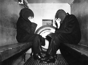 Estos importantes hombres con zapatos de charol se esconden del fotógrafo con ayuda de su sombrero, 1941.