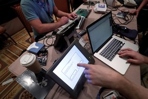 FILE PHOTO: Hackers try to access and alter data from an electronic poll books in a Voting Machine Hacking Village during the Def Con hacker convention in Las Vegas, Nevada, U.S., July 29, 2017. REUTERS/Steve Marcus/File Photo