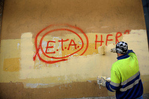 FILE PHOTO: A municipal worker paints over graffiti reading ETA, The People Are With You in Guernica, Spain, October 21, 2011, the day after Basque separatist group ETA announced a definitive cessation of armed activity. REUTERS/Vincent West/File photo