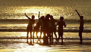 Un grupo de jóvenes disfruta del atardecer en la playa de La Concha de San Sebastián. Las temperaturas máximas han llegado a los 19 grados en la capital guipuzcoana